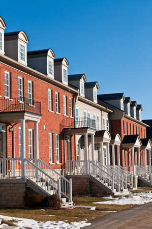 A row of recently built townhouses on a suburban street in winter. photo