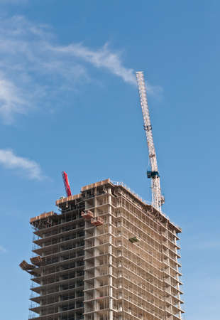 A high rise building under construction with tower crane. photo