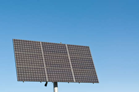 A photovoltaic solar panel array in a park with a deep blue sky in the background. Clean, renewable energy. photo