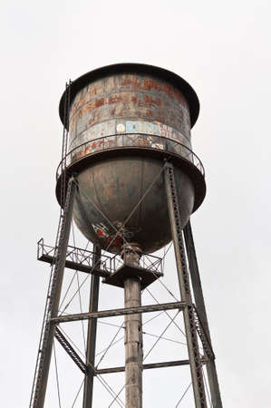 An old water tower covered with rust and graffiti. photo