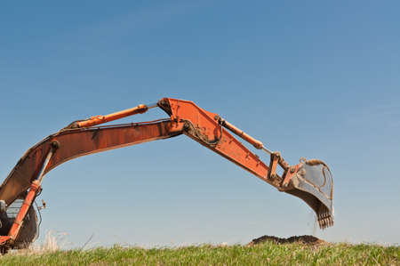 The arm and bucket of a hydraulic excavator that is digging into a grassy hilside. photo