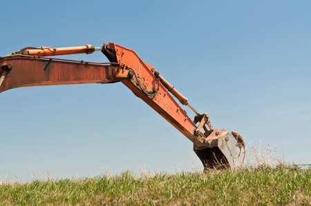 The arm and bucket of a hydraulic excavator that is digging into a grassy hilside.