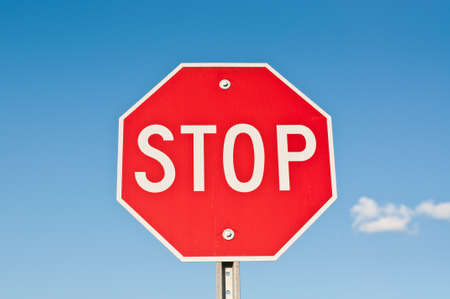 with stop sign: A red octagonal stop sign with blue sky and clouds in the background.