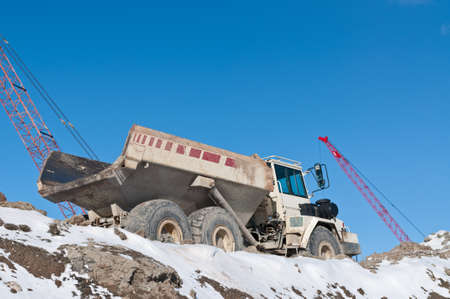A dump truck sits on top of a pile of earth at a construction site in winter with two cranes in the background.