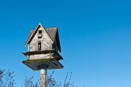 A birdhouse sits atop a pole with a deep blue sky in the background.