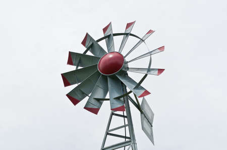 A small windmill spins and generates electricity with a grey sky in the background.