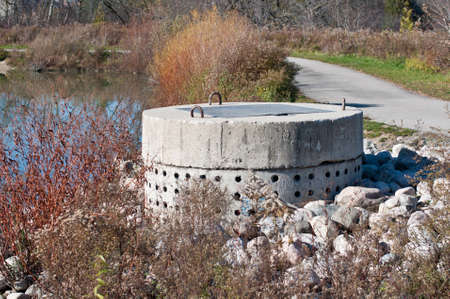 A perforated concrete pipe forms part of a stormwater management system in a suburban pond.