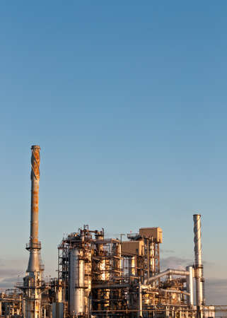 A petrochemical refinery plant in the evening with pipes and cooling towers. Stock Photo
