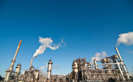 A petrochemical refinery plant with pipes and cooling towers. Stock Photo