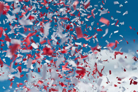fill fill in: Red and white strips of paper confetti fill the air with a blue sky and white clouds in the background. Stock Photo
