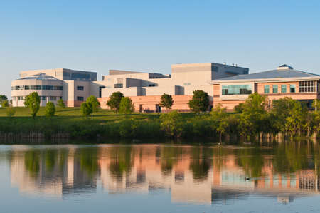 A community center building surrounded  by a park is shown reflected in the water of a large pond. Stock Photo