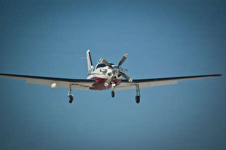 A small single-engined aircraft approaches the runway with its landing gear down.