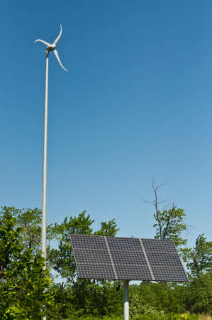 A wind turbine and a photovoltaic solar panel stand next to each other in a park.