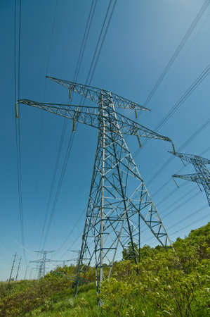 A long line of electrical transmission towers carrying high voltage lines. Imagens