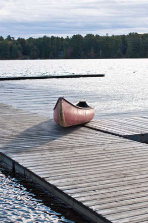 A red canoe is pulled up onto a dock on a lake in Muskoka, Ontario, Canada. photo