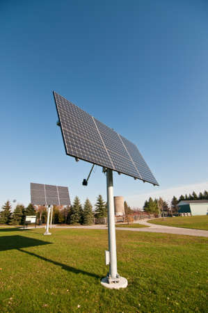 Moveable solar panels stand in a park.