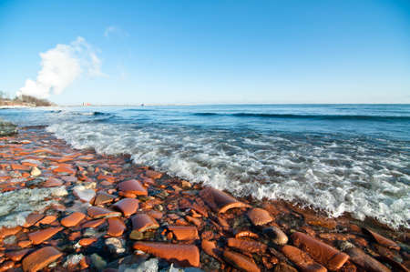 A beach on Lake Ontario is covered with broken pieces of clay pipe.