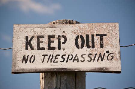 no trespassing: Un degradado cartel clavado en un poste que dice: Keep Out - Prohibido el paso. Letras negras en se�al de blanco.
