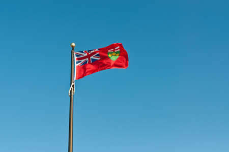 The provincial flag of Ontario flies on a flagpole with a deep blue sky in the background.