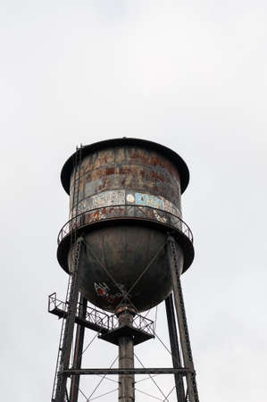 An old water tower covered with rust and graffiti. Stock Photo