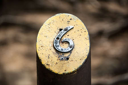metal post: A number six is fastened to a painted metal post along a path