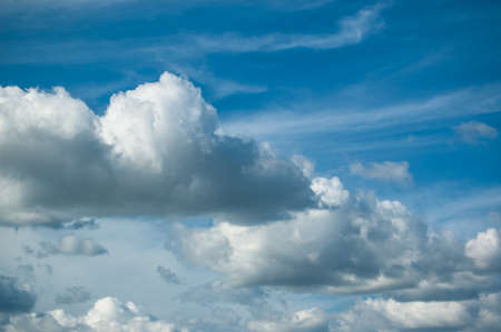 A variety of different types of clouds in a deep blue sky.