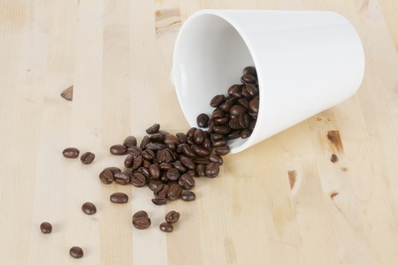 Picture of coffee beans and a white cup on a table photo