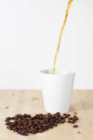 Picture of coffee beans and a white cup on a table Coffee being poured in the cup photo