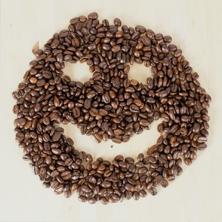 Picture of a smiley face made of coffee beans photo
