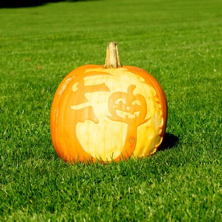 Picture of a pumpkin, with silhouette of a witch and a pumpkin cut in the surface Standing on a lawn photo