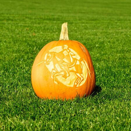 Picture of a pumpkin, with silhouette of a knight and horse cut in the surface Standing on a lawn photo