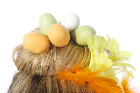 Picture of a girls hair formed as a nest, with easter eggs in it, on a white, isolated background photo