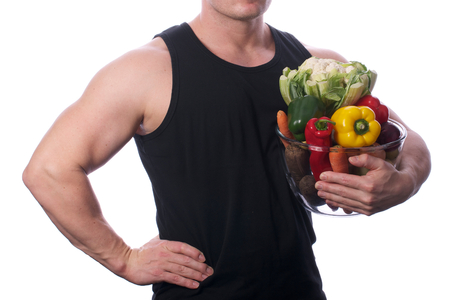 Picture of a fit, muscular arm or body holding vegetables or fruit, on a white, isolated background  Picture of a fit, muscular arm or body holding vegetables or fruit, on a white, isolated background
