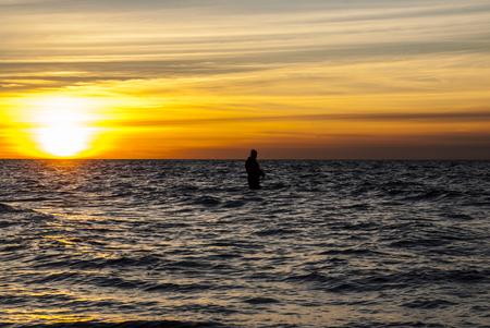 botas altas: Pescador en la puesta del sol del otoño en la costa, de la foto de Brian Holm Nielsen