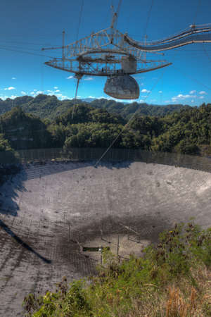 ionosphere: Arecibo Observatory radio telescope in Puerto Rico as seen from the observation deck. The radio telescope was built in the 1960s and is the worlds largest single aperture telescope. The diameter of the dish is 1000 feet or about 305 meters.