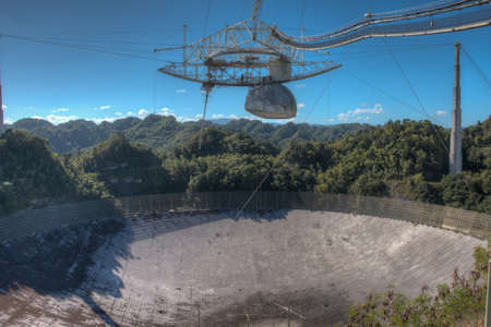 telescope: Arecibo Observatory radio telescope in Puerto Rico as seen from the observation deck. The radio telescope was built in the 1960s and is the worlds largest single aperture telescope. The diameter of the dish is 1000 feet or about 305 meters.