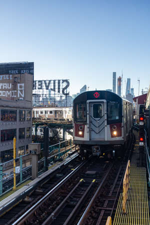 New York, NY / USA - Oct. 14, 2020:  A vertical sunset view of the number 7 subway train pulling into  an el station in Queens. Silvercup sign and Manhattan's skyline visible in the distance.