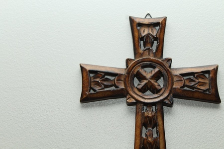 a wooden cross, Celtic style, on the right side of the frame with light shining from overhead