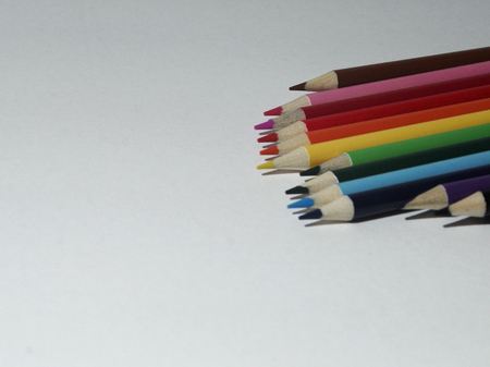 Colored Pencils laid side by side from the upper right corner with scattered tips