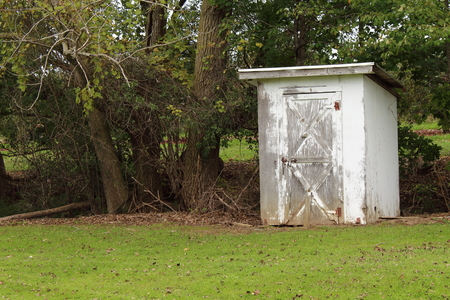 Small white storage shed in a field next to a river