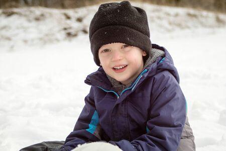 Winterjunge lächelnd im Schnee sitzend