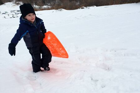Young Winter Boy Climbing Hill With Orange Sled