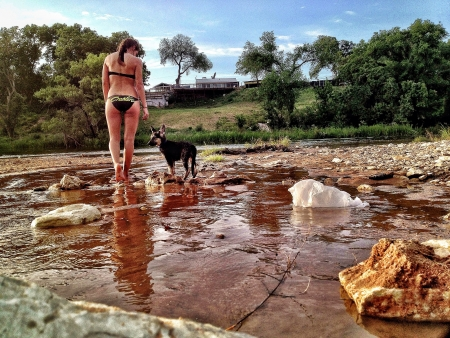 Woman and German Shephard puppy in a lake
