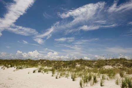 Clouds forming behind a grass covered dune at Huntington Beach, South Carolina.