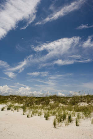 Beautiful clouds forming over grass covered dunes.