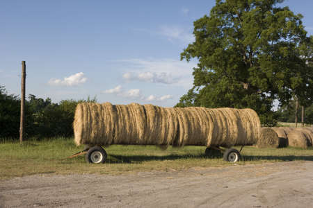 On the side of a country road sits a large trailer full of hay bails. Stock Photo