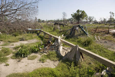 Heavily damaged homes in the Ninth Ward of New Orleans. One block behind these homes is the industrial canal that collapsed during the storm surge of hurricane Katrina. Nothing but a bike and some framing lumber remain on this lot.