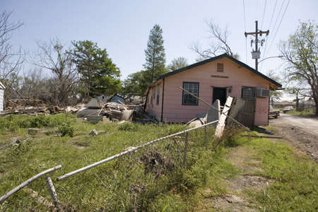 fled: A pink wood house in the heavily damaged section of New Orleans Ninth Ward.  The flood waters from hurricane katrina have knocked the home off its foundation and carried it across the property, ultimately setting it down almost in the street.  Stock Photo