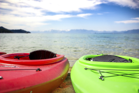 Colorful kayaks resting by the lake Stock Photo