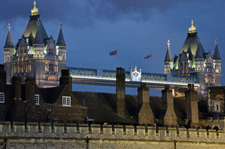 The flags of the United Kingdom and England fly from Tower Bridge fronted by the Tower of London